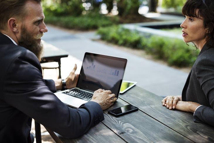 שני אנשים יושבים בפארק ומדברים, מול מחשב נייד
