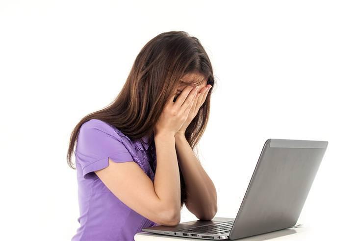 אישה יושבת מול מחשב נייד ומכסה את פניה בידיה