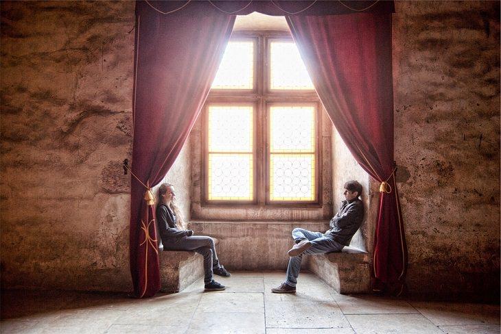 ללמוד פסיכולוגיה: גבר ואישה יושבים אחד מול השני בתא עם וילון