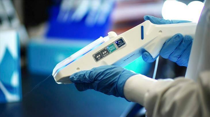 אקדח לטיפול בכוויות: ידיים עטויות כפפות אוחזות באקדח העור