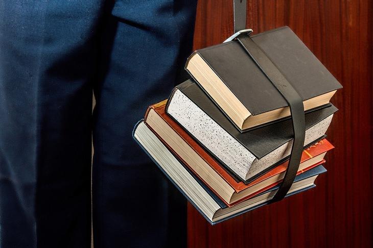 6 טיפים להורים לקראת החזרה ללימודים: איש עומד ומחזיק לצדו ספרים שקשורים יחדיו בעזרת חגורה