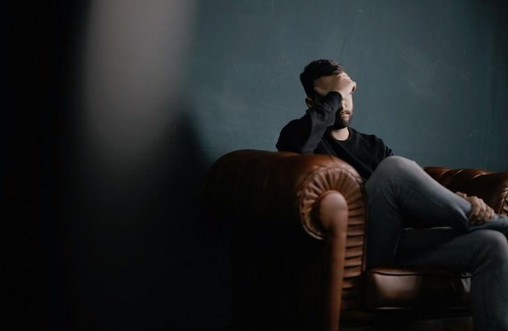 סימנים מבלבלים לאהבה בזוגיות: גבר עם יד על פניו יושב על שפה