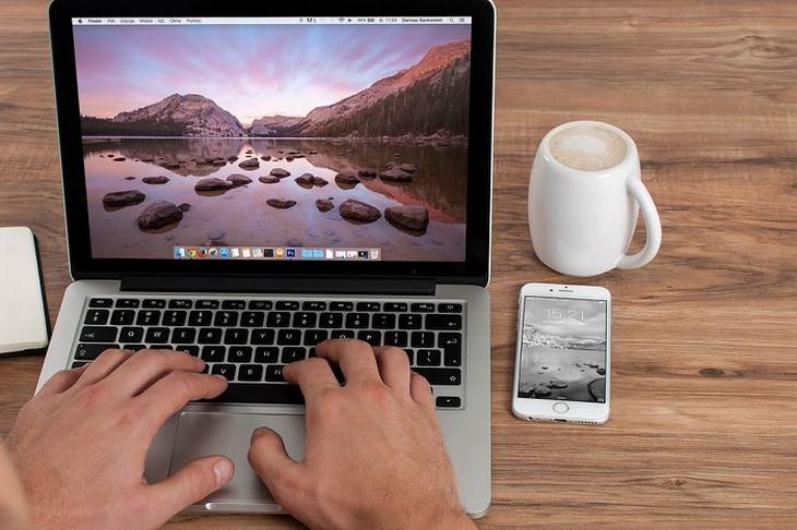 סיבות לעקצוץ ברגליים ובידיים: איש מקליד על מחשב נייד שנמצא על שולחן לצד כוס קפה וסמארטפון