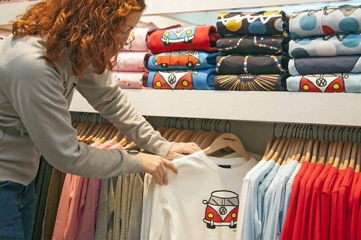 טכניקות של אנשי מכירות: אישה בוחנת חולצות על קולב בחנות בגדים