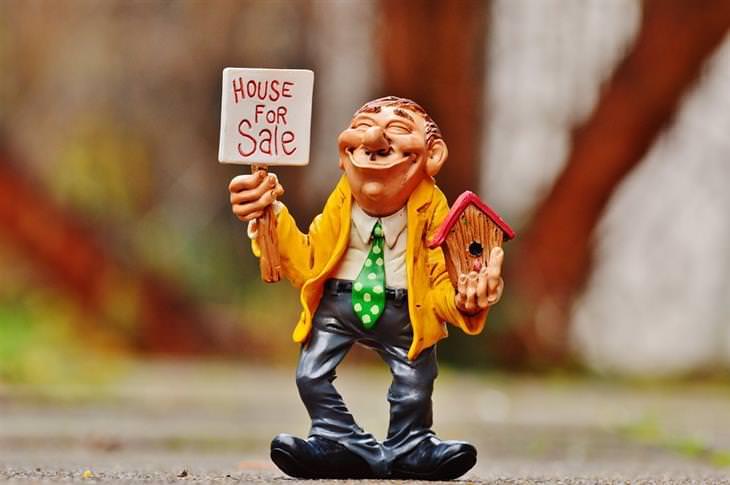 """טכניקות של אנשי מכירות: בובה של איש בחליפה, מחזיק שלט """"בית למכירה"""" ביד אחת ושובך לציפורים ביד שנייה"""