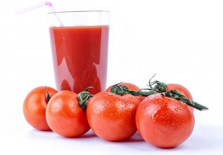 מניעת הזעת יתר בצורה טבעית: עגבניות מונחות ליד כוס עם מיץ עגבניות