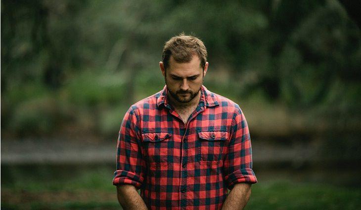 איך לשפר מצב רוח רע: גבר מביט לאדמה במבט מדוכדך