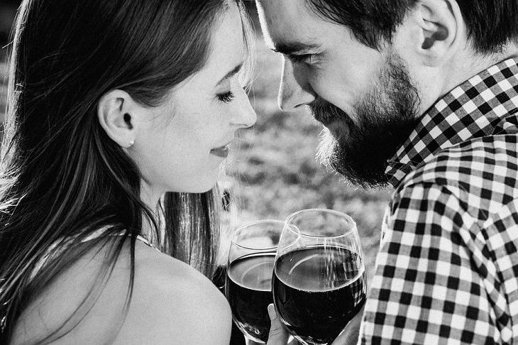 הרגלים של זוגות עם חיי מין מוצלחים: גבר ואישה מביטים אחד על השנייה עם כוסות יין ביד