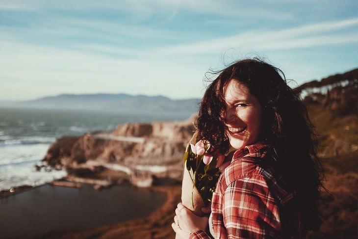 פעולות לעשות היום שישפיעו עליכם לטובה: אישה אוחזת בזר פרחים על חוף ים ומחייכת למצלמה