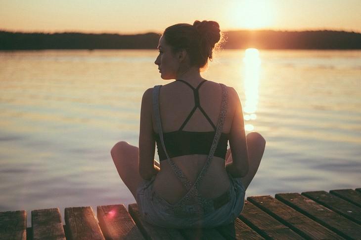 פעולות לעשות היום שישפיעו עליכם לטובה: אישה יושבת על מזח מול שקיעה