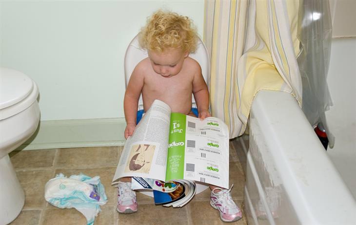 שאלות נפוצות ותשובות בנוגע לתהליך גמילה מחיתולים: ילד יושב על אסלה עם ישבנון ומסתכל במגזין