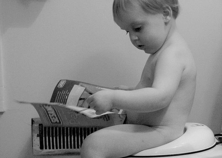 שאלות נפוצות ותשובות בנוגע לתהליך גמילה מחיתולים: ילד יושב על אסלה ומסתכל על מגזין