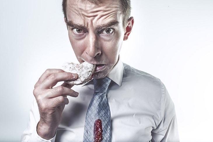 דברים שאסור לעשות על בטן ריקה: אדם בעל מבט עצבני נוגס בסופגניה