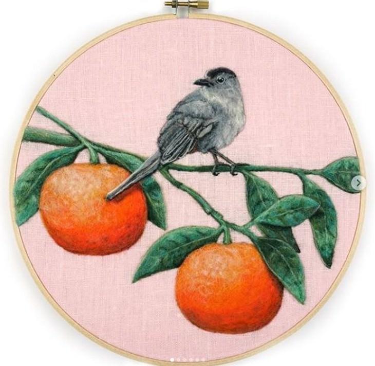 רקמות לבד של חיות: ציפור עומדת על ענפים של תפוזים