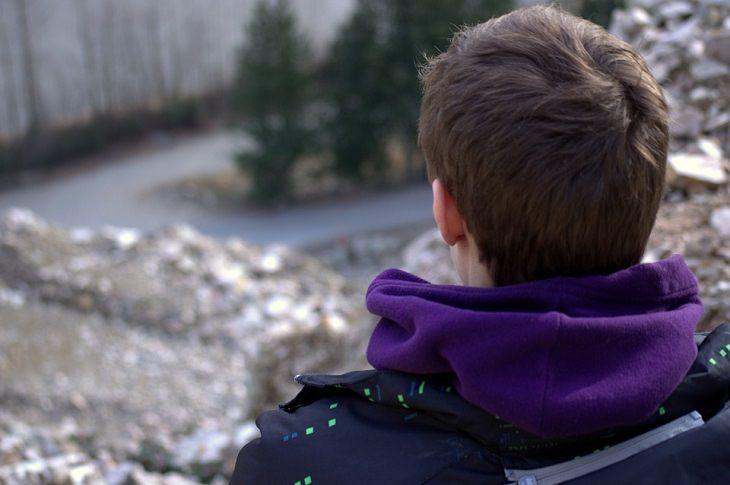 סיבות וטיפולים לגירוד בראש: בחור יושב בגבו למצלמה