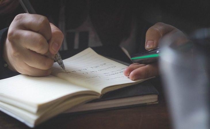 """שיטות חינוך בארה""""ב: ילד כותב במחברת ומחזיק מחשבון"""