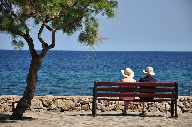 סודות לזוגיות מאושרת: זוג יושב על ספסל מול הים