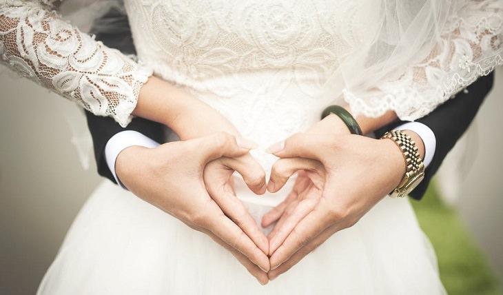 חתונה ברבנות: זוג בבגדי חתונה יוצר צורת לב עם הידיים