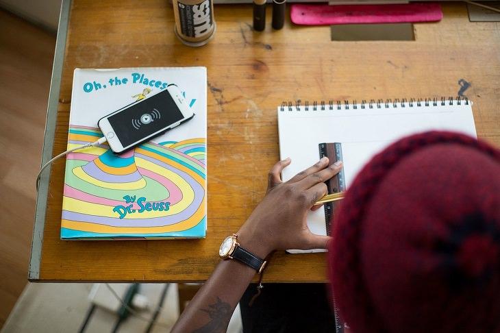 סגנונות למידה אצל ילדים: ילד משרטט במחברת כשלצידו הסמארטפון שלו