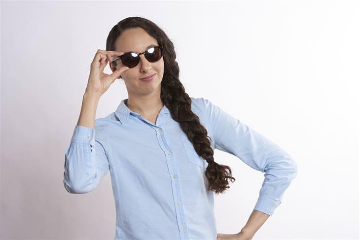 איך להתמודד עם אנשים קשים: אישה מחזיקה במשקפי שמש שעל פניה