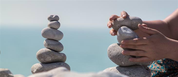 איך להתמודד עם אנשים קשים: ידיים של איש שבונה מגדל מאבנים