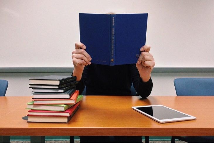 סימנים שאתם בדרך הנכונה: גבר יושב מול שולחן עם ספרים, אוחז בספר פתוח מול פניו