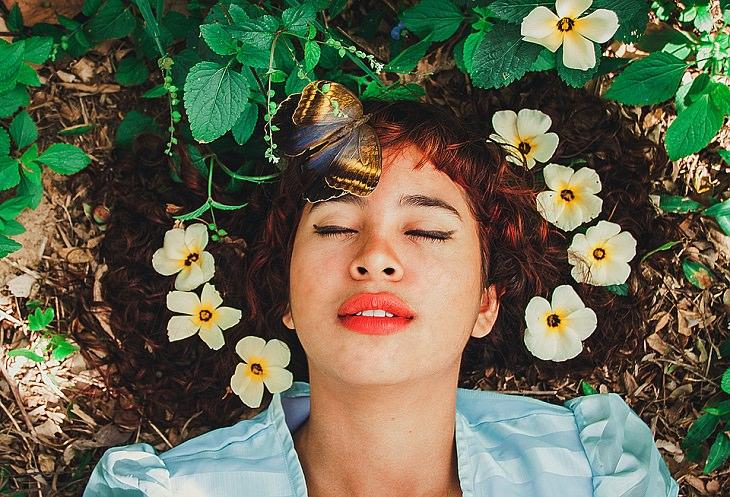 סימנים שאתם בדרך הנכונה: אישה שוכבת על האדמה, מוקפת פרחים, פרפר ועלים
