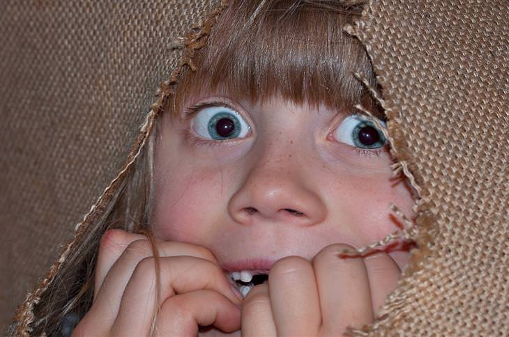 מדריך להתמודדות עם פחדים נפוצים של ילדים בכל גיל: ילדה מפוחדת מסתתרת מאחורי בד