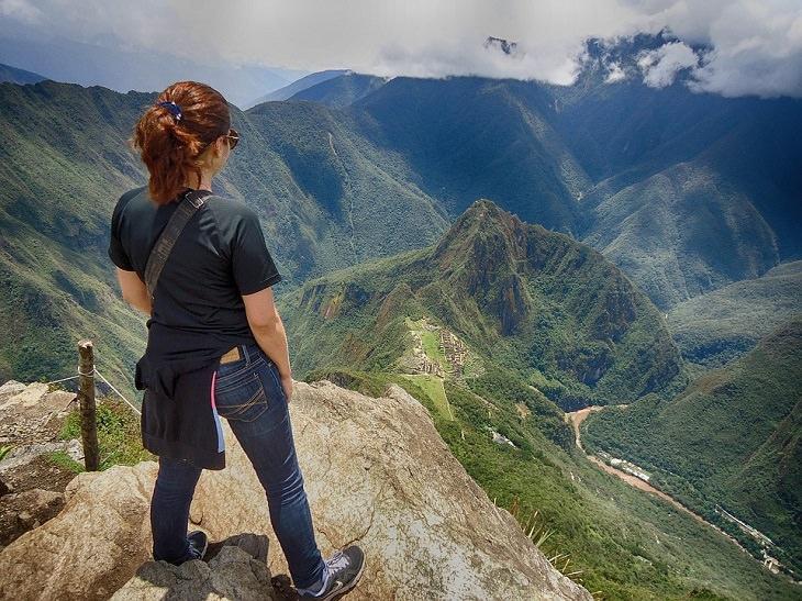 לאהוב את עצמנו: אישה עומדת על קצה הר ומביטה על הנוף ההררי