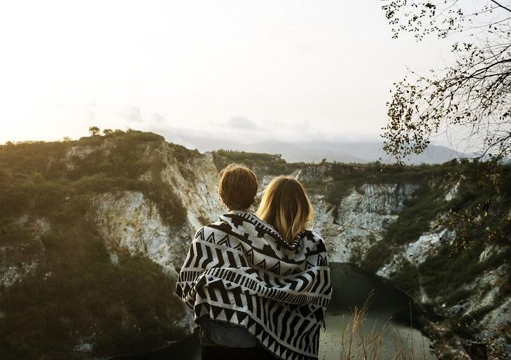 לאהוב את עצמנו: זוג מחובק ועוטה שמיכה מביט על נוף הרים ואגם