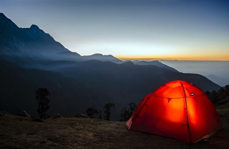 לאהוב את עצמנו: אוהל מואר באור אדום על נוף ים והרים