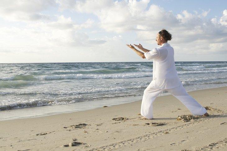 יתרונות הצ'י קונג: אדם לבוש לבן המתרגל צ'י קונג בחוף הים