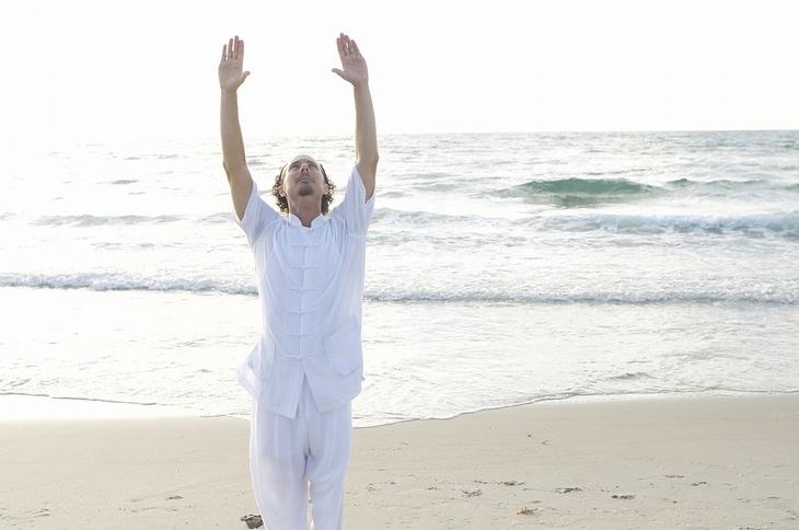 יתרונות הצ'י קונג: אדם לבוש לבן, מניף ידיו לשמיים בחוף הים