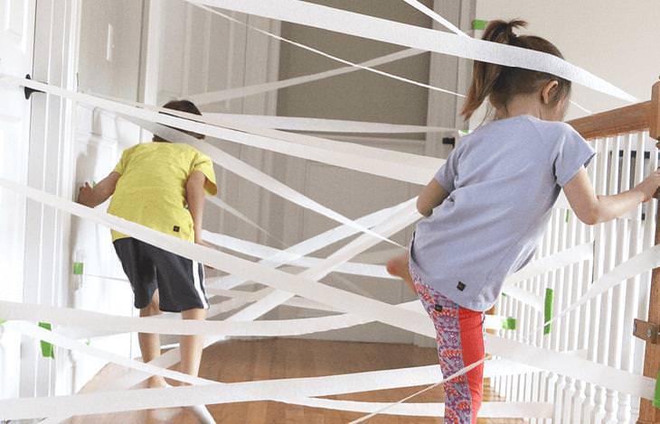 משחקים ביתיים שיגרמו לילדים להפעיל את הגוף והמוח: ילדים משחקים במסלול מכשולים