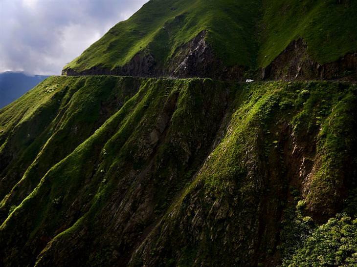 תמונות אוויריות של גאורגיה: רכב עם נהג אמיץ נוהג בכביש ההררי הצר בדרך לתושתי
