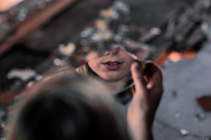 """עצות זוגיות של ד""""ר פיל: אישה מביטה על החלק התחתון של פניה דרך מראה שבורה"""