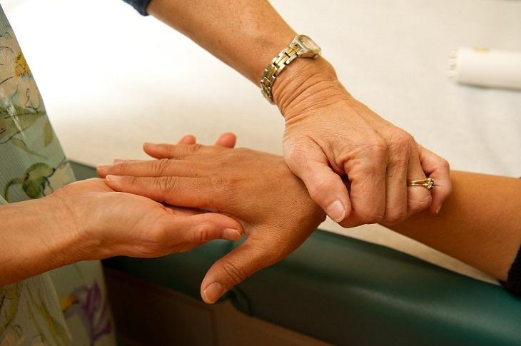 מידע על מחלת הפרקינסון ודרכי מניעתה: יד אחות אוחזת ביד חולה