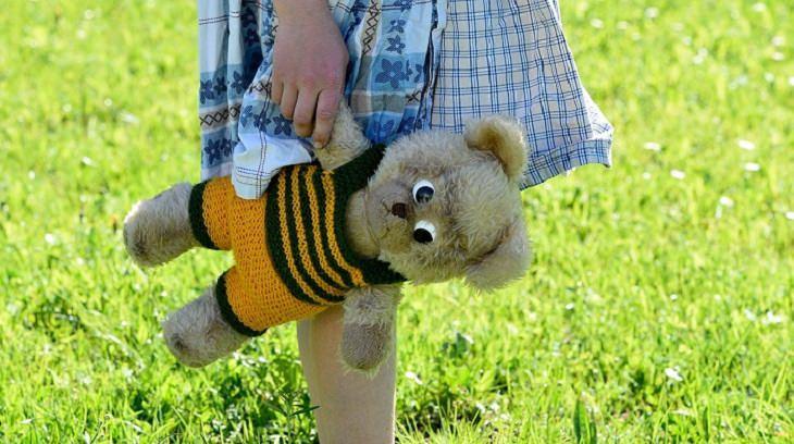 הסיבות שמאחורי בעיות התנהגות של ילדים - ילדה מחזיקה בובת דובי על רקע דשא