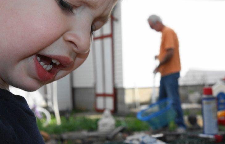הסיבות שמאחורי בעיות התנהגות של ילדים - ילד בגינה עם אדם מבוגר ברקע