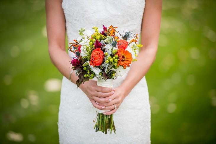 בדיחה על איש זקן שהתחתן עם צעירה: ידיים של כלה אוחזות בזר פרחים
