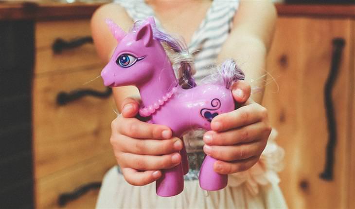 טיפים מאמהות חכמות: ילדה מחזיקה צעצוע של סוס פוני
