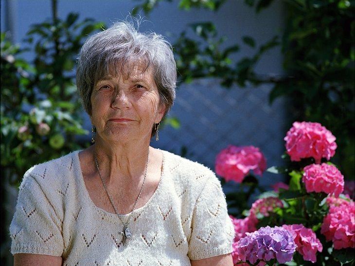 שיר על הברכה שבשכחה: אישה מבוגרת יושבת ליד פרחים בגינה