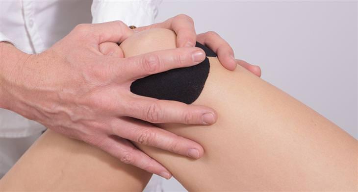 יתרונות בריאותיים של שמן קריל: תקריב של ידיים של רופא שבודקות ברך של מטופל