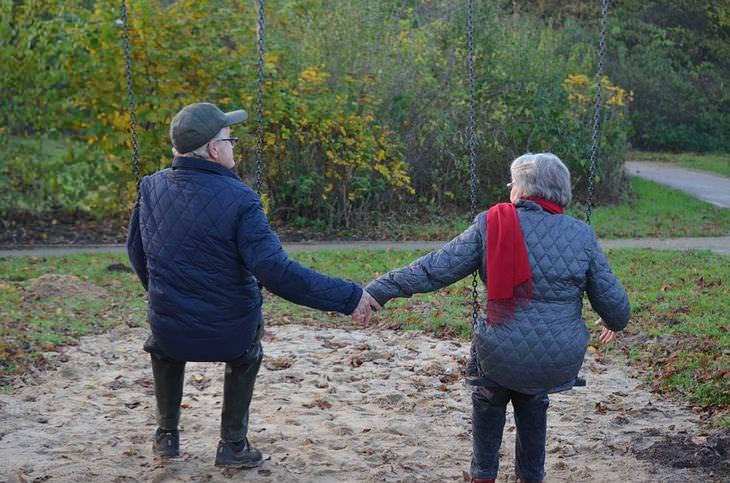 ריבים נורמליים בין בני זוג: זוג מבוגר מתנדנד על נדנדות בפארק ואוחז ידיים