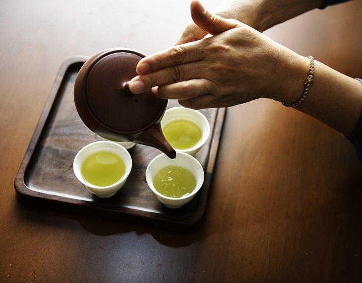 יתרונות ומתכון לחליטה תה אורגנו: ידיים מוזגות תה מקנקן תה לכוסות על מגש