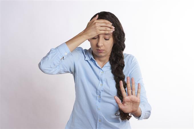 אישה אוחזת בראשה ומחזיקה יד אחת מולה