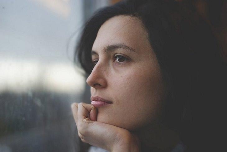 מילים שאתם צריכים להפסיק להגיד לעצמכם: אשה מסתכלת בחלון במבט מהורהר