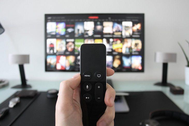 מדריך להוזלת עלויות הטלוויזיה: יד מחזיקה שלט מול טלוויזיה
