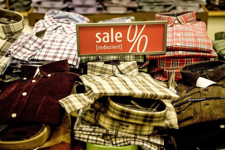 """דברים שאתם צריכים לדעת על כסף מגיל צעיר: בגדים מסודרים על מדף ולידם שלט """"מבצע"""""""
