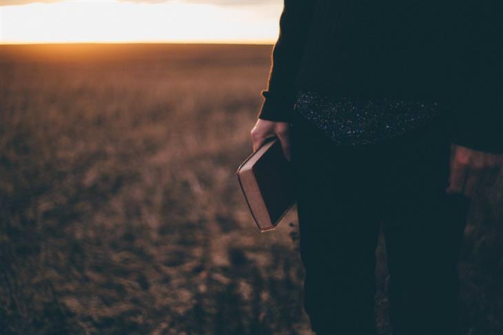קבלת החלטות נבונות בעזרת מודל פירמידת דילטס: אישה מחזיקה ספר ועומדת בשטח פתוח